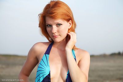 Freckled redhead Mia Sollis takes off her swimsuit as the ocean waves roll in