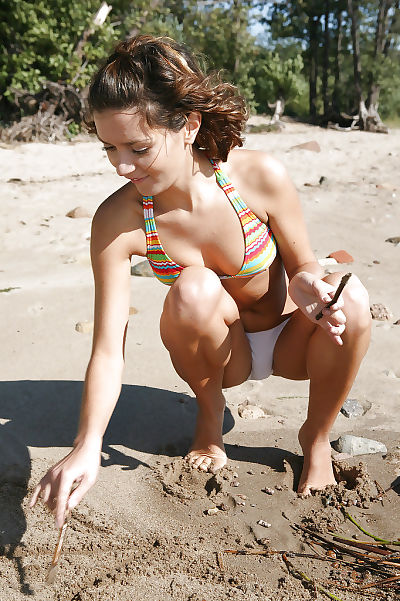 Grubby youthful brown hair delightsome off her bikini and toying her muff outdoor